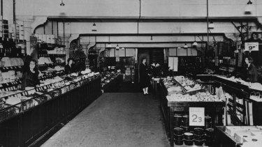 """A section of Woolworths' original """"Bargain Basement"""" which opened in the Imperial Arcade, December 5, 1924. A sales docket and the customer's money were propelled by overhead wire to the cashier in her """"eagle's nest"""" at top right. The receipt and change were then returned to the counter by the same method."""