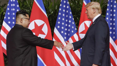 President Donald Trump reaches to shake hands with North Korea leader Kim Jong-un at the Capella resort on Sentosa Island in Singapore.