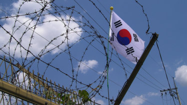 The South Korean flag seen through barbed wire at the DMZ, in Panmunjeom, South Korea.