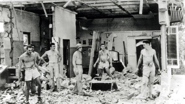 Troops inspect the remains of a building following the raid.