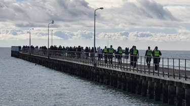 People lining the Rye Pier over the June long weekend to fish for spider crabs.