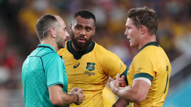 Referee Romain Poite speaks with Samu Kerevi and captain Michael Hooper during Australia's match with Wales.