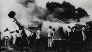 """""""The burning fuselage of the Qantas BOAC Constellation which burst into flames upon landing at Singapore's Kallang Airport today."""" March 13, 1954"""