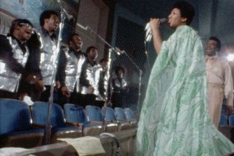 Aretha Franklin waited until the last song to stand up and face the choir.