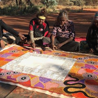 Lead artist Rene Kulitja (third from left) supervises artists Christine Brumby, Charmaine Kulitja and Happy Reid.