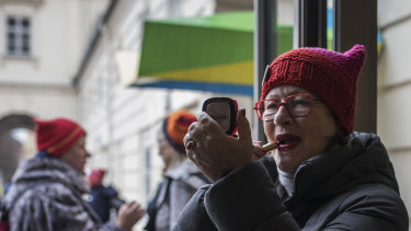 Susanne Scholl applies make-up before the demonstration against racism in Vienna last month.