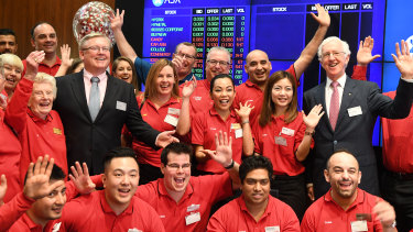 Coles managing director Steven Cain (in suit, left) and chairman James Graham (right) with Coles staff at its ASX listing ceremony on Wednesday.