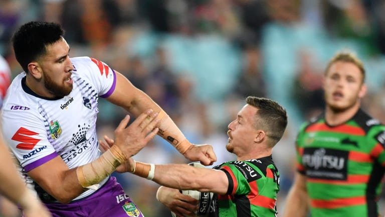 Playing above his weight: Damien Cook clashes with the Storm's Nelson Asofa-Solomona