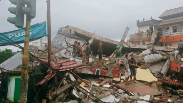 Residents inspect earthquake-damaged buildings in Mamuju, West Sulawesi, Indonesia, on Friday.