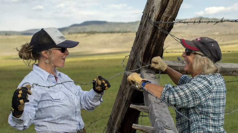 Caitlyn Taussig and her mother, Vicki, mend fences on their ranch in Kremmling.