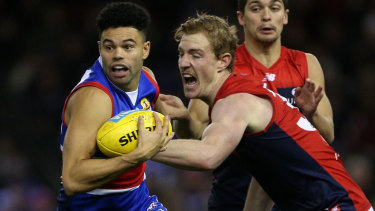 Jason Johannisen of the Western Bulldogs fends off Melbourne's Harrison Petty in round 17.