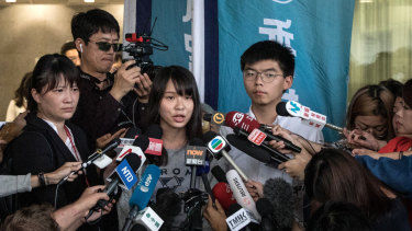 Hong Kong pro-democracy activists Agnes Chow and Joshua Wong speak to the media after being arrested and released on bail.