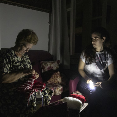 Residents sitting in torchlight during Beirut's nightly power cuts. Some places will get electricity for only an hour or two a day.
