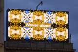 'Never alone' by artist KentMorris,a digital billboard on St Kilda's intersection between Grey and Fitzroy Streets. Part ofACCA's major exhibition in 2021,Who's Afraid of Public Space?