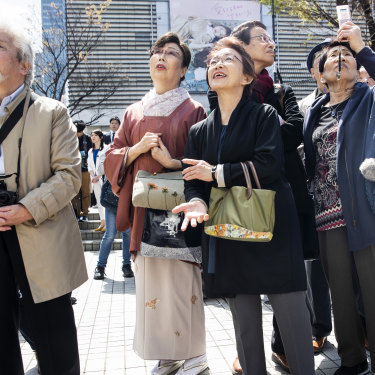 Pedestrians in Tokyo watch as the name of the new era is unveiled on April 1.