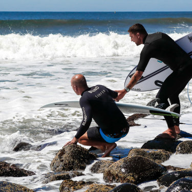 Assisted by Michael Crisp, Formston becomes half-man, half-crab to navigate the boulders edging the challenging Lennox Point surf break.