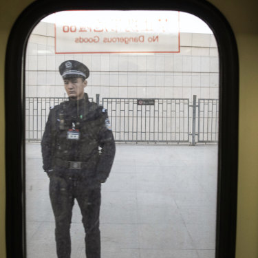 A police officer seen through a train window in Turpan, Xinjiang, in 2018.