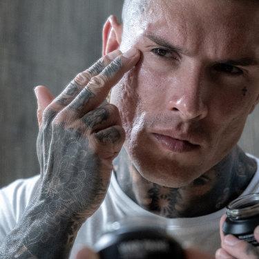 A model applying War Paint concealer. Make-up targeted at Australian men.