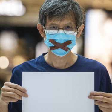 Protesters have been warned they may be in breach of national security laws for raising blank pieces of paper, as this demonstrator did on June 6.
