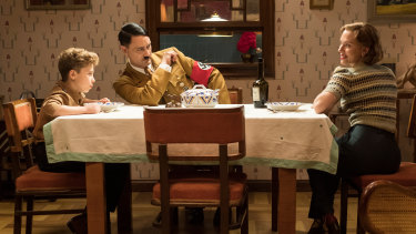 Jojo (Roman Griffin Davis) has dinner with his imaginary friend Adolf (writer/director Taika Waititi), and his mother, Rosie (Scarlett Johansson).