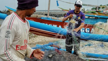 Taufik a fisherman from Kedonganan, Bali cleaning and untangling plastic trash caught on his fishing net.