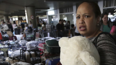 A Cuban doctor clutching a teddy bear prepares to depart the airport with her colleagues in Brasilia, after they were recalled by the Cuban government.