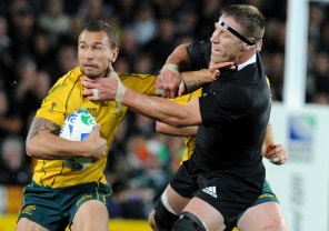Quade Cooper fends off Brad Thorn at the 2011 Rugby World Cup.