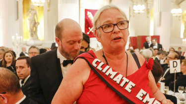 A climate change protester walks through the dining tables during the annual Bankers and Merchants Dinner during Philip Hammond, UK chancellor of the exchequer's speech at The Mansion House in London, UK.
