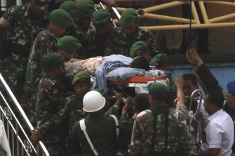 Soldiers carry Wiranto on a stretcher to a waiting helicopter to be evacuated to Jakarta.