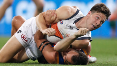 Toby Greene wrestles with Brisbane's Luke Hodge during Saturday night's final at The Gabba.
