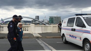 An elderly climate activist is arrested on South Brisbane's William Jolly Bridge on Friday.