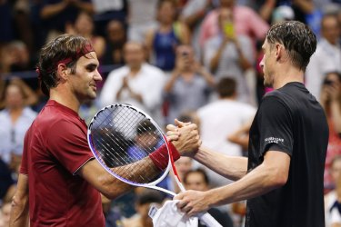 John Millman and Roger Federer shake hands after the Australian won their match at the US Open in 2018.