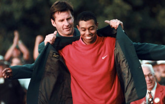 Where it all began: Nick Faldo presents Tiger Woods with his first green jacket in 1997.