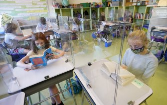 Students wearing face masks are separated by plexiglass at a school in New York state.