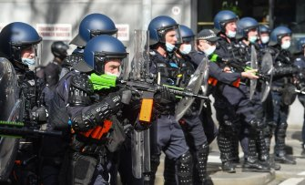 Police fire pepper spray pellets at protesters near Victoria Market on Saturday.