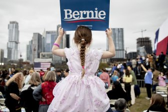 Lily Barbour, 5, holds up a campaign sign for Democratic presidential candidate Bernie Sanders.