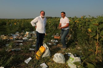 Paul McGeough (left) amid the wreckage of MH17 on the outskirts of Rassypnoye in eastern Ukraine.