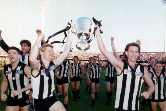 Collingwood players celebrate with the premiership trophy.