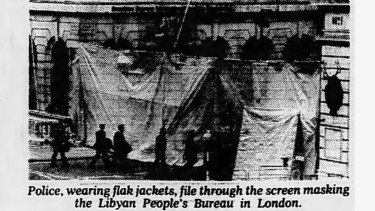 Police, wearing flak jackets, file through the screen masking the Libyan People's Bureau in London - Clipped from The Age.