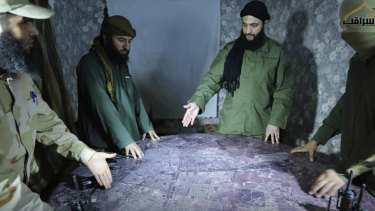 Abu Mohammed al-Golani of the militant Levant Liberation Committee and the leader of Syria's al-Qaeda affiliate, second right, discusses battlefield details with field commanders over a map, in Aleppo, Syria. Golani has vowed to fight on in Idlib province, in the face of a possible government offensive.
