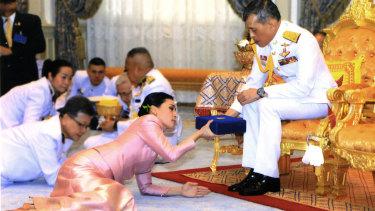 King Maha Vajiralongkorn presents a gift to Queen Suthida Vajiralongkorn Na Ayudhya at Ampornsan Throne Hall in Bangkok.