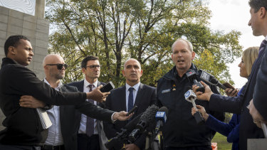 The MCC's Stuart Fox, AFL's Travis Auld and Victoria Police Commander Tim Hansen hold a press conference to address the recent violence at AFL matches.