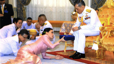 King Maha Vajiralongkorn presents a gift to Queen Suthida Vajiralongkorn Na Ayudhya at Ampornsan Throne Hall in Bangkok.