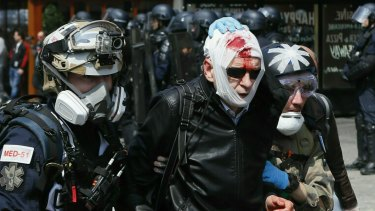 A man, his face covered in blood, is helped to leave during a May Day demonstration in Paris on Wednesday.