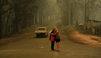 Residents comfort each other in Nelligen, west of Batemans Bay, on January 1, after fire destroyed homes.