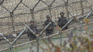 South Korean army soldiers patrol along the barbed-wire fence in Paju, South Korea, on Friday.