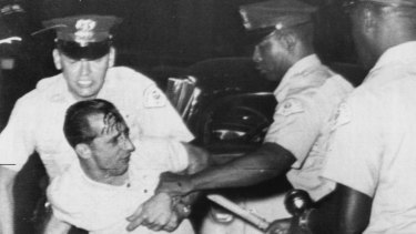 Despite a bloodied head, a white demonstrator grapples with police after fights broke out between black and white people when three black families moved into a predominantly white Chicago suburb in 1963.