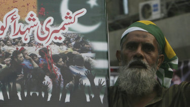 "A Pakistani holds a placard that reads, ""salute to Kashmiri martyrs,"" during an anti-Indian protest in Karachi, Pakistan."