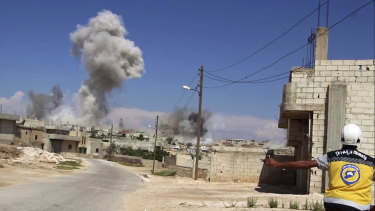 A civil defense worker watches as smoke rises from a Syrian government airstrike, in Hobeit village, near Idlib.