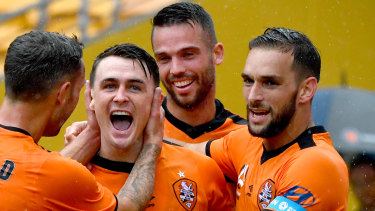 Dylan Wenzel-Halls (centre) of the Roar celebrates scoring a goal with Scott McDonald (left) and Jack Hingert (right).
